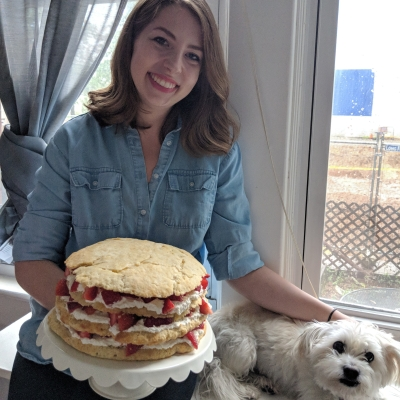 Kitra holding a cake and petting her dog