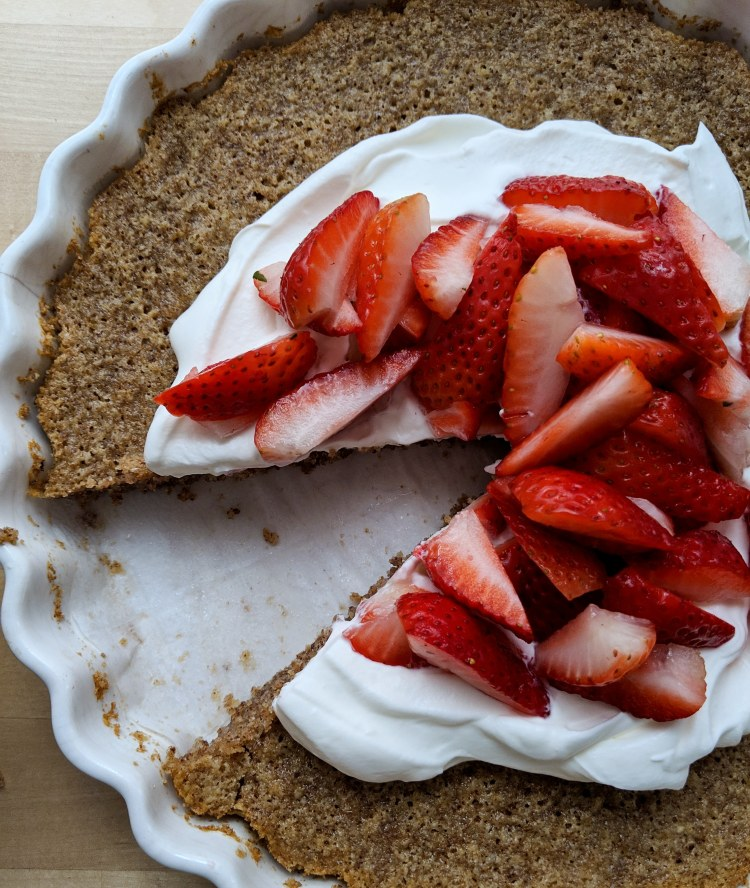 Pecan browned butter cake, topped with whipped cream and strawberries and missing a slice