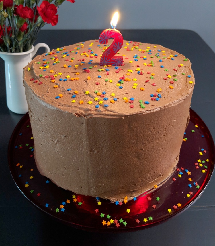 Three-layer cake with chocolate frosting, sprinkles, and a lit candle