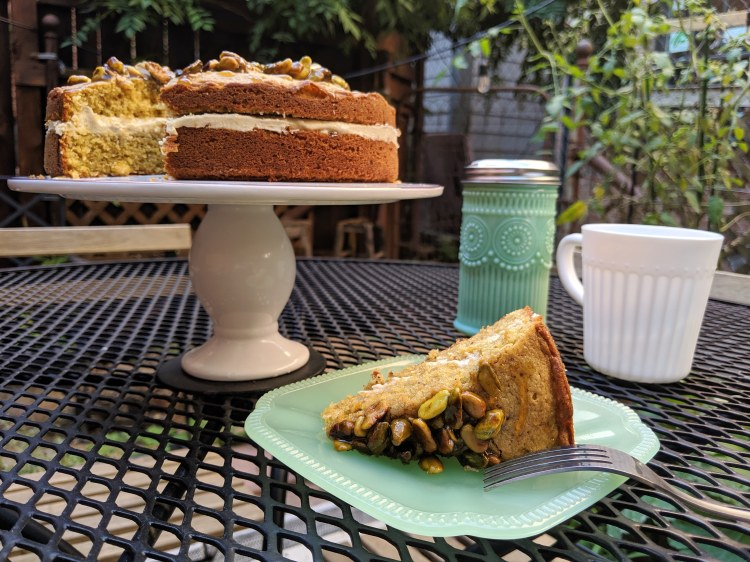 Slice of honey pistachio cake on a plate with the full cake and a mug in the background