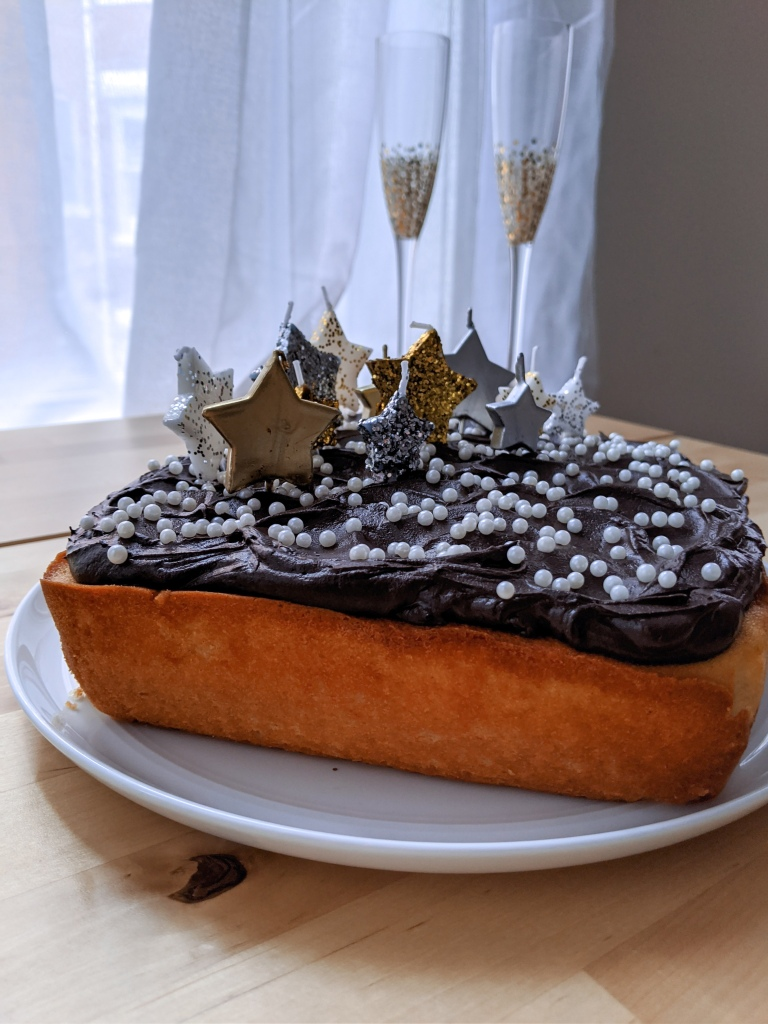 A cake with chocolate frosting, large white sprinkles, and many glittery star-shaped candles