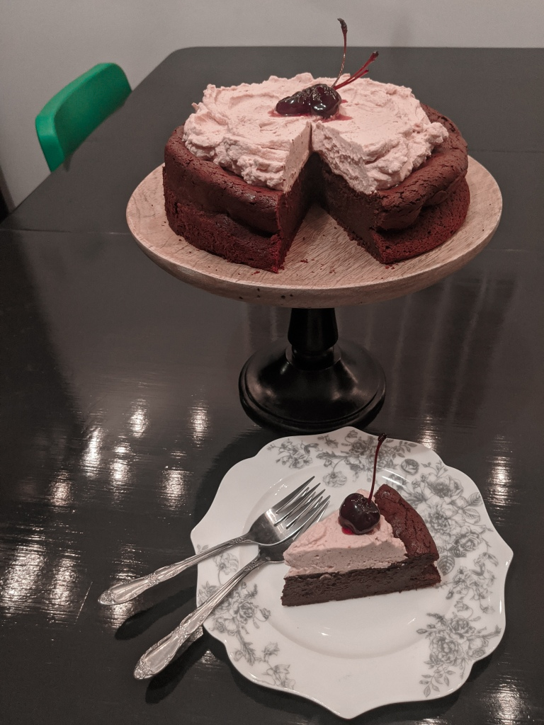 A chocolate cake with black cherry whipped cream, with a slice cut out and sitting on a plate with two forks.
