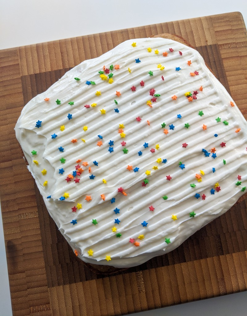 A square spice cake with white frosting and star-shaped sprinkles.