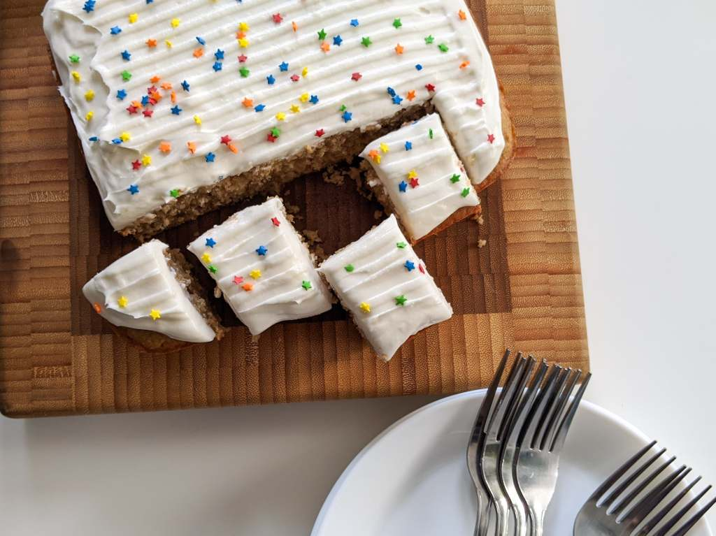 A square spice cake with white frosting and star-shaped sprinkles. Several pieces have been cut from the cake to be served.