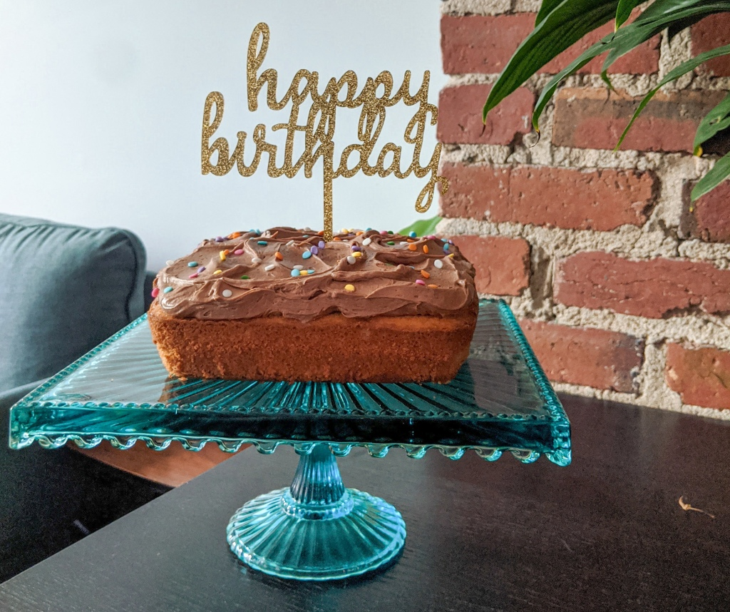 "A cake with chocolate frosting with a sparkly sign reading ""happy birthday"" in cursive, on a blue glass cake stand"