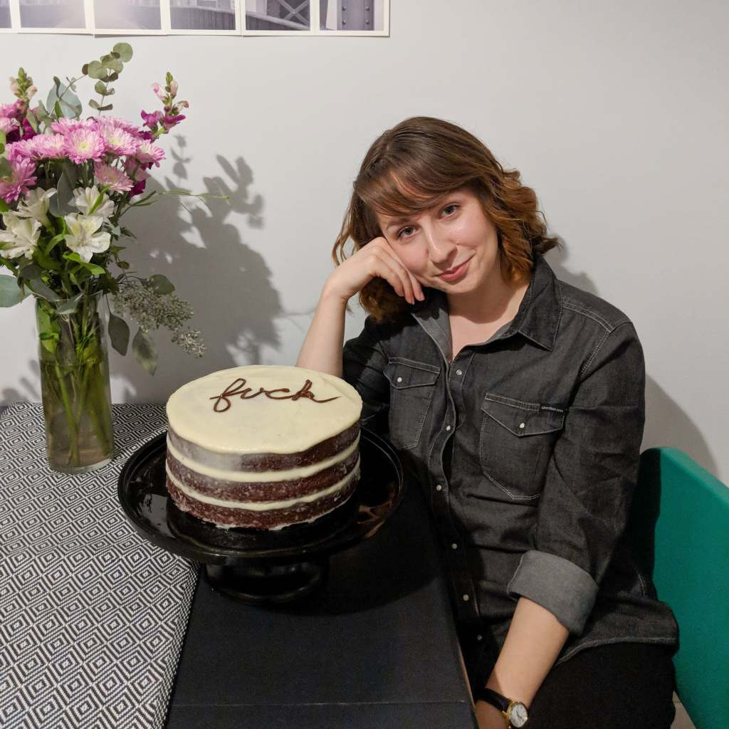 "Jordan (a young woman in a denim shirt) sitting next to a layered cake that reads ""fuck"" in cursive frosting"