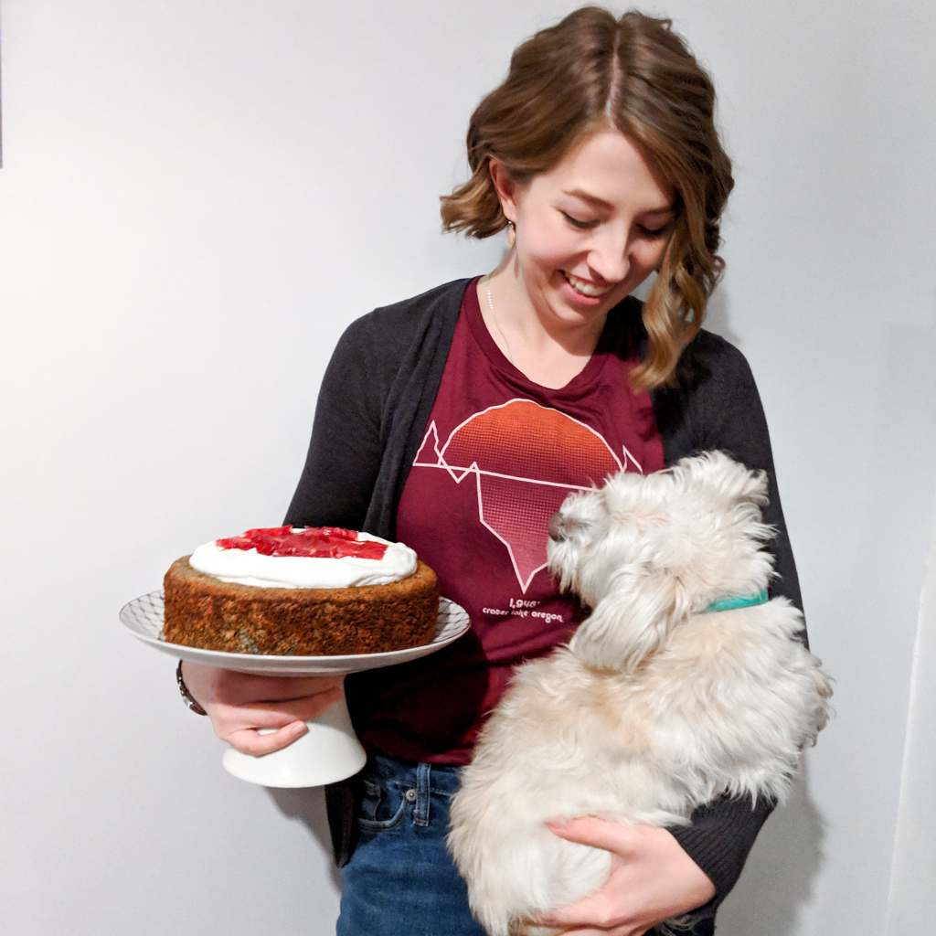 Kitra  (a young woman with short curly hair) holds a cake stand and a small dog.