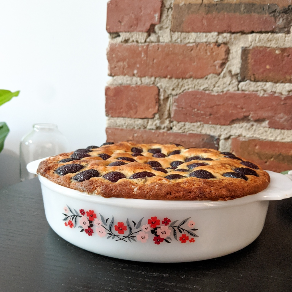 A cake with cherries pressed in the top baked in a flowery Pyrex dish