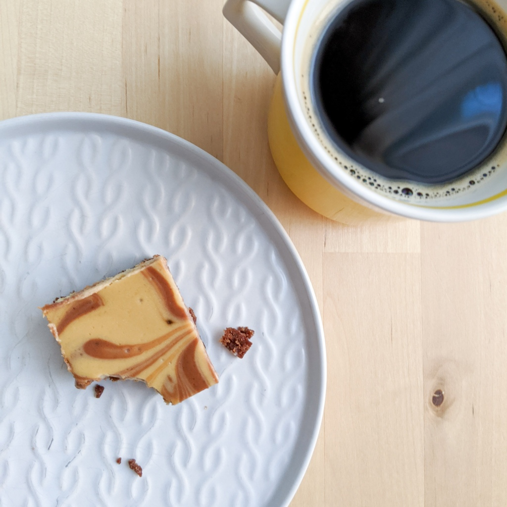A square of marbled chocolate/coffee cheesecake with a bite missing, next to a cup of coffee