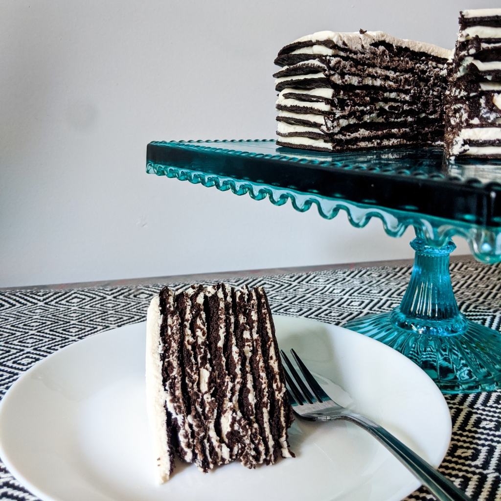 A layer cake made of large chocolate cookies and whipped cream