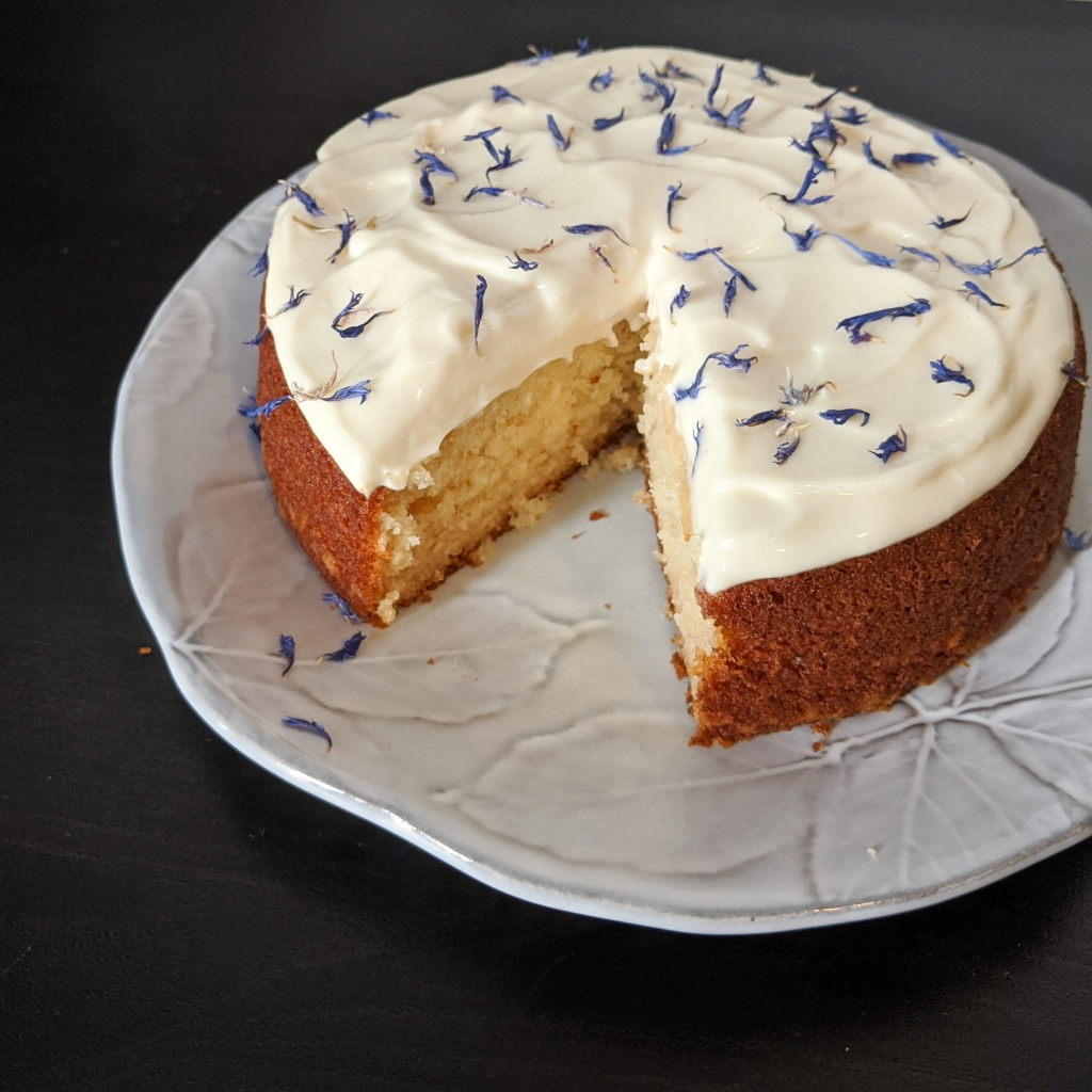 A round honey cake with cream cheese frosting and dried blue flowers on top