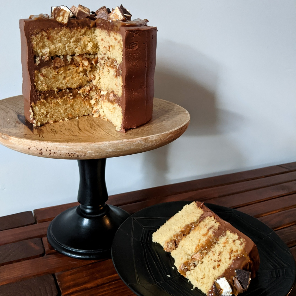 A small three-tier caramel cake with dulce de leche and candy chunks in between the layers and chocolate frosting on the outside, all resting on a wooden cake stand. A slice of the cake is on a plate next to it.