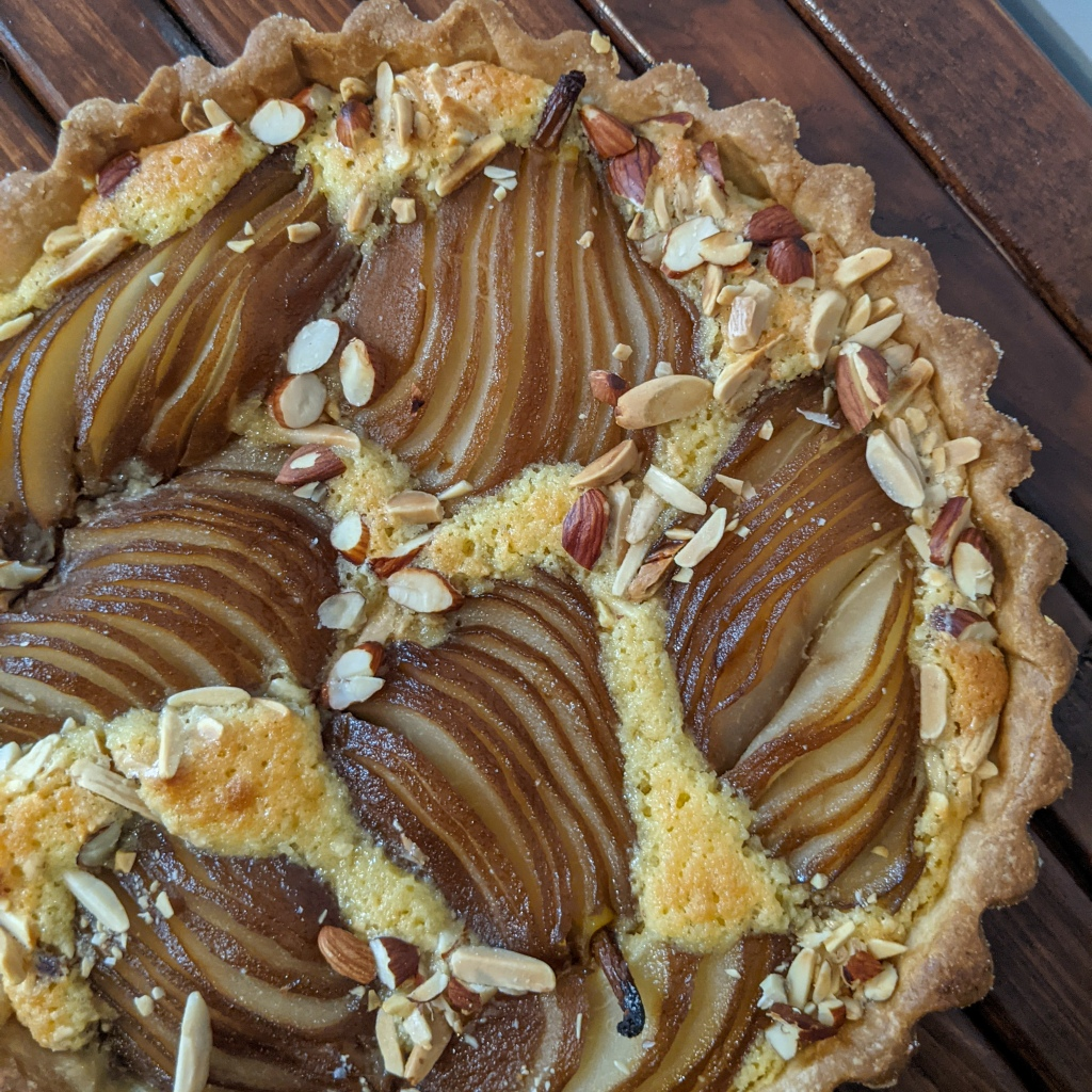 Top-down image of an almond tart with whole sliced pears baked into it