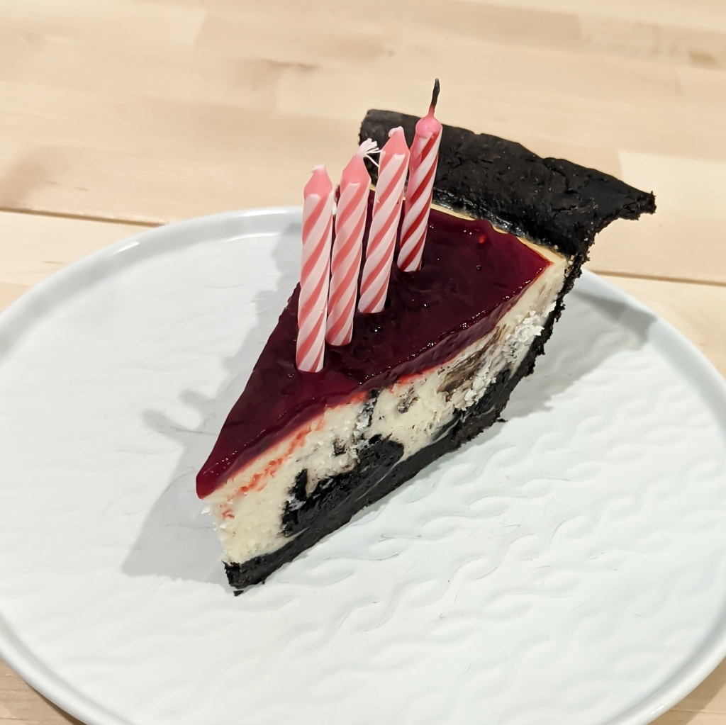 A slice of chocolate-swirled cheesecake with chocolate crust, raspberry topping, and four pink birthday candles