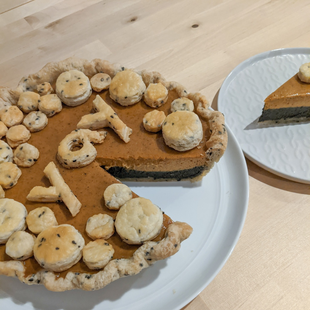 "A layered pumpkin and black sesame pie with one slice cut out; the top is covered in circles of pie crust and the word ""yay"" spelled in crust"