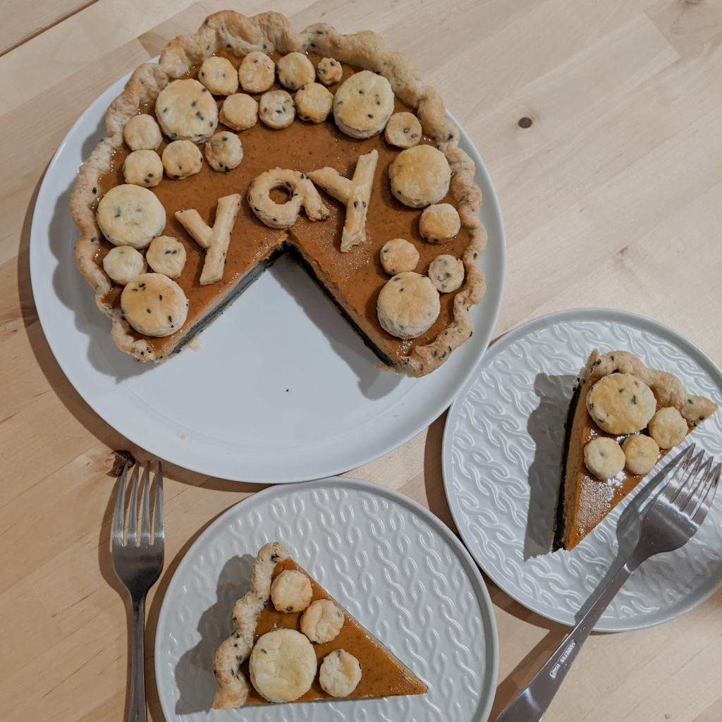 "A top-down shot of a layered pumpkin and black sesame pie with two slices cut out; the top is covered in circles of pie crust and the word ""yay"" spelled in crust"