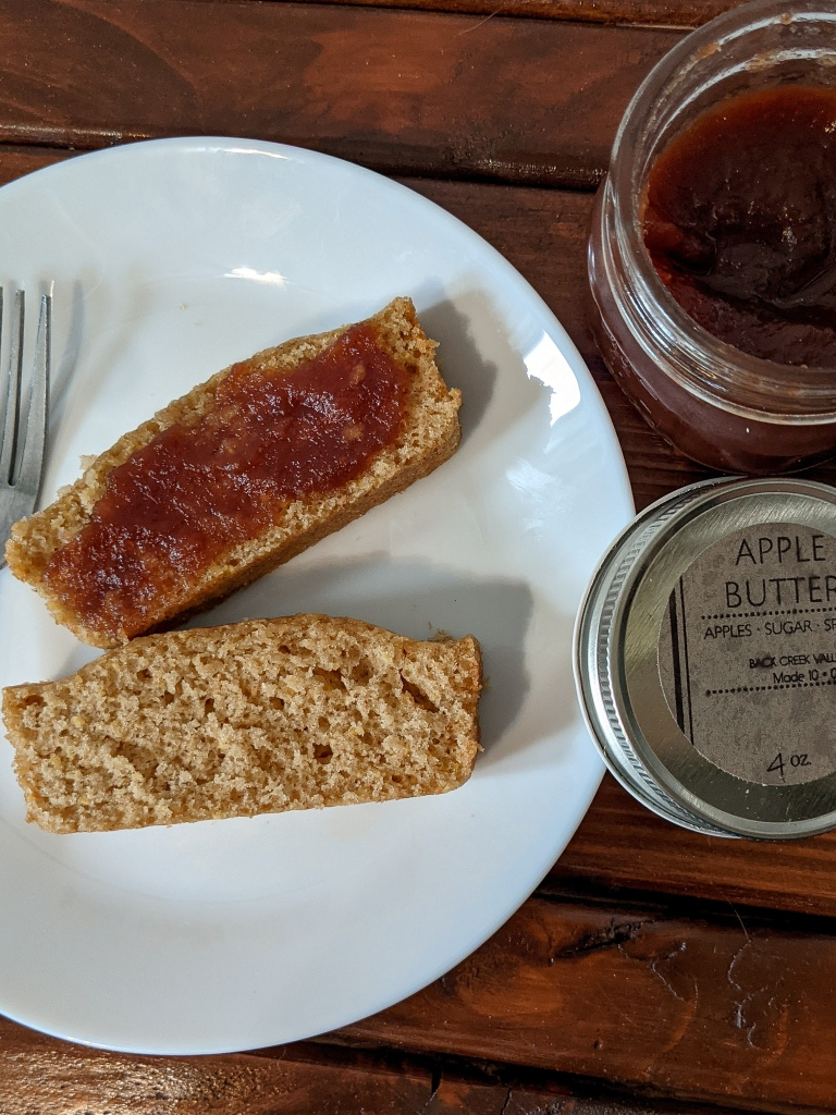 Two slices of brown sugar cake, one with apple butter spread on top, with a jar of apple butter open next to the plate