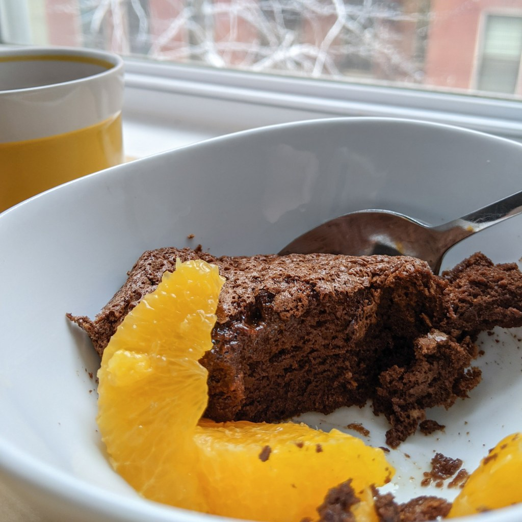 A scoop of chocolate pudding cake and some orange segments in a bowl with a mug of tea alongside.
