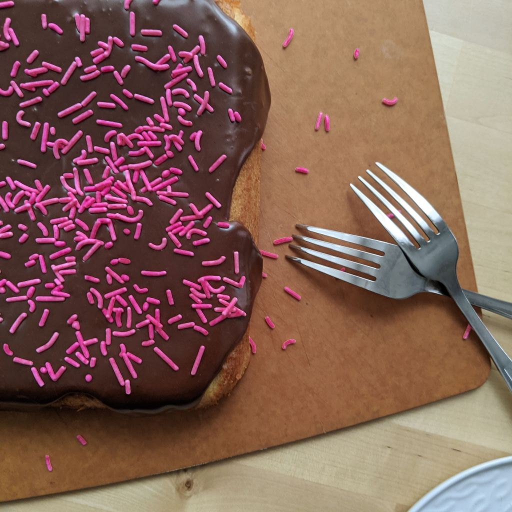A chocolate-glazed cake with pink sprinkles on top and two forks resting next to it