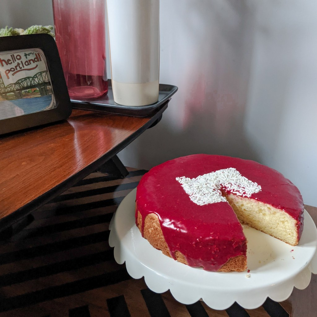 A well-decorated side table with a pink-glazed cake resting on a cake stand. The cake has the shape of the state of Oregon on the top in white sprinkles.