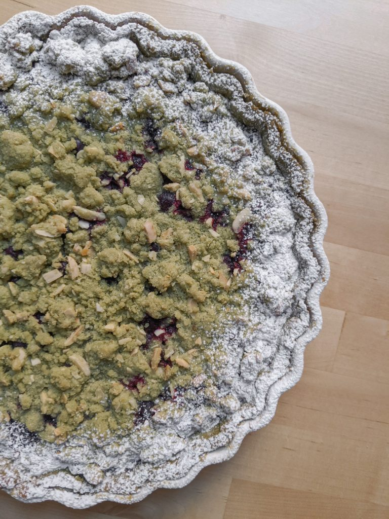 A top-down view of a green matcha streusel tart with blueberries peeking through the topping and powdered sugar around the edges