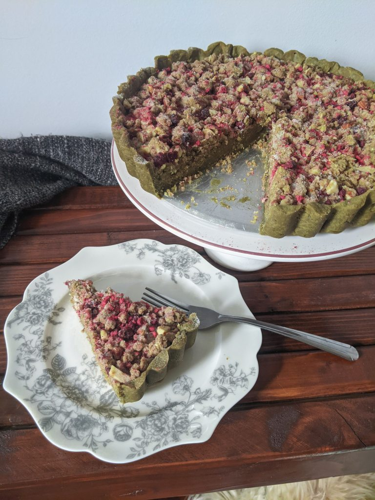 A a green matcha streusel tart with dried raspberries in topping; a slice has been cut out and placed on a plate next to it.