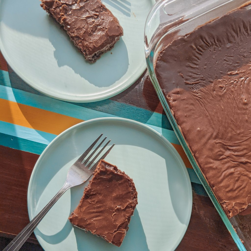 Two slices of iced chocolate cake sitting on plates alongside a pan of cake