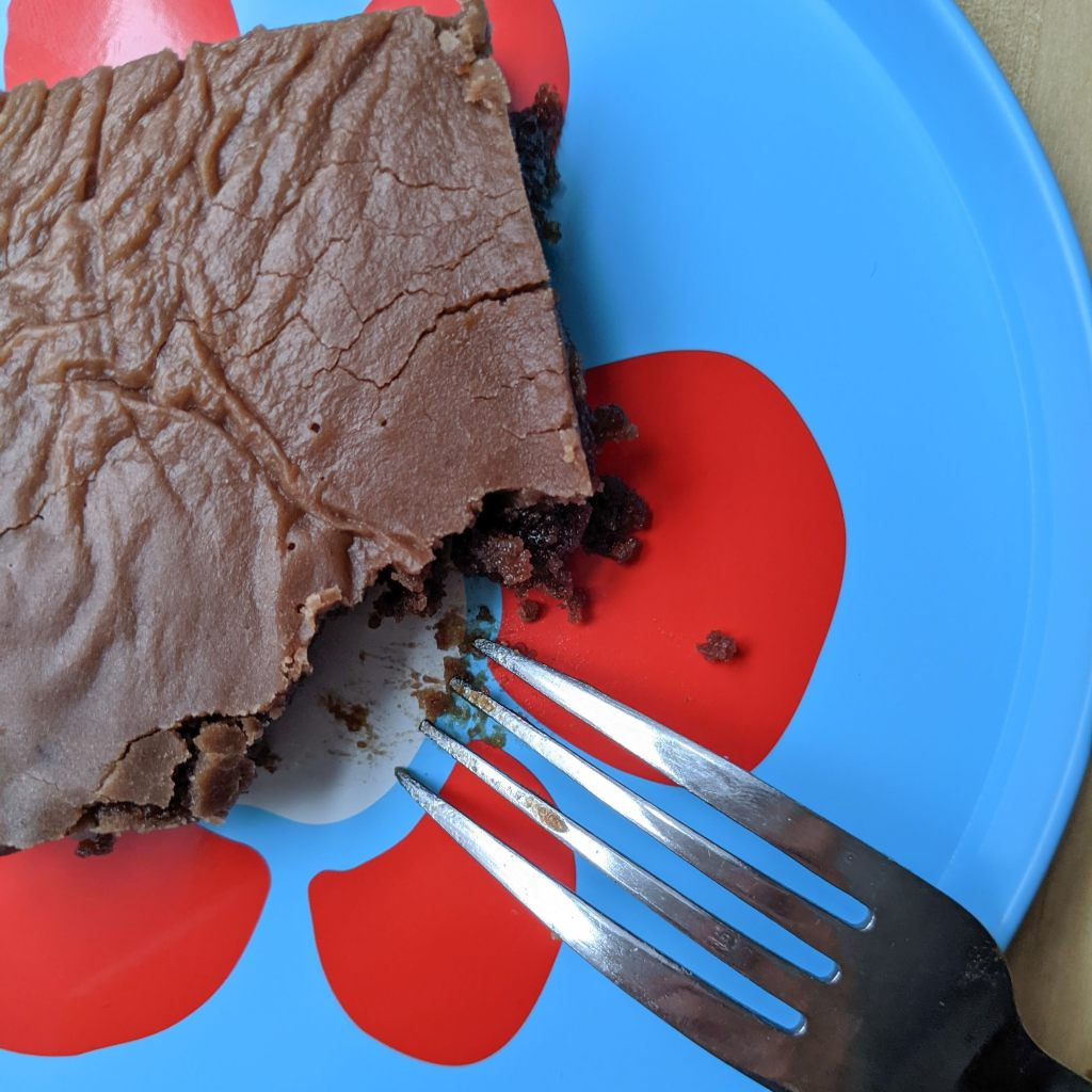 A square or iced chocolate cake with a forkful taken out