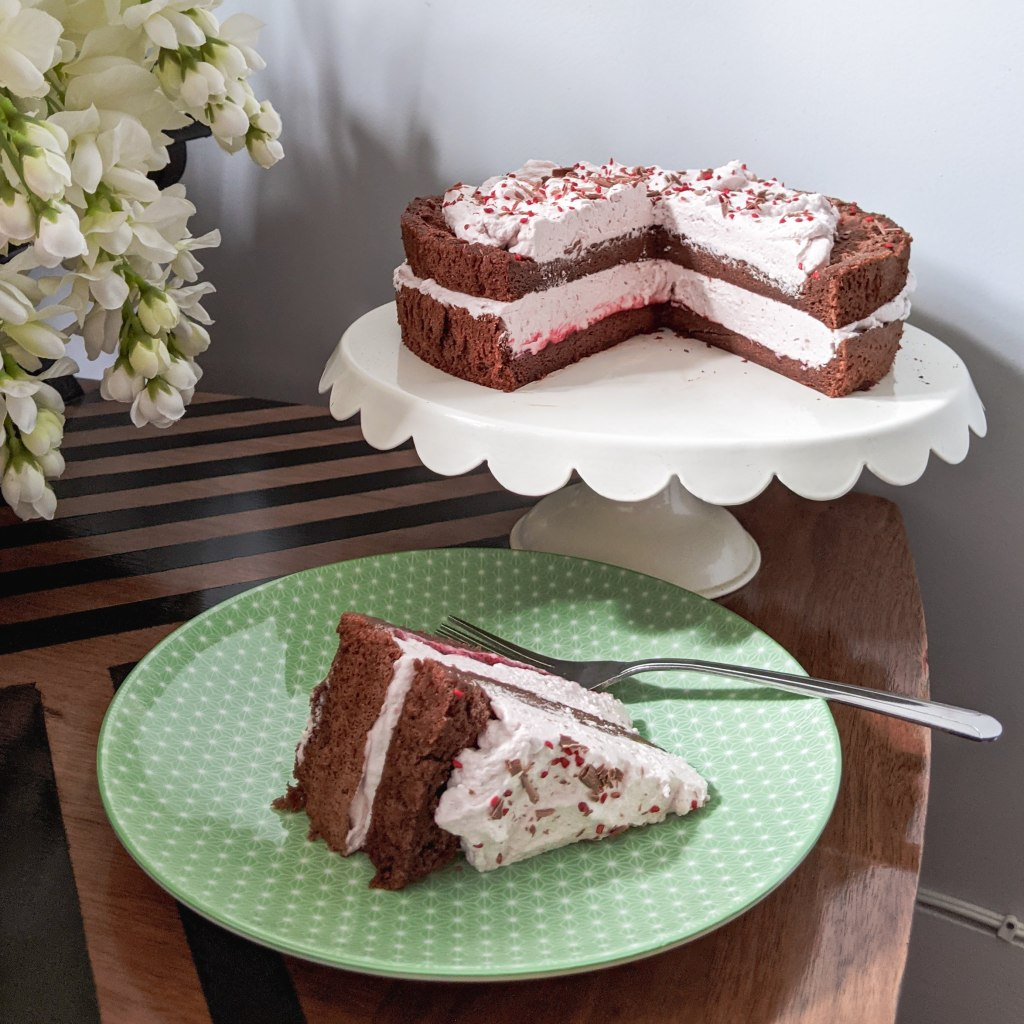 A chocolate cake with pink whipped cream on top and between the layers; a slice has been cut out and is sitting on a green plate next to the cake stand.
