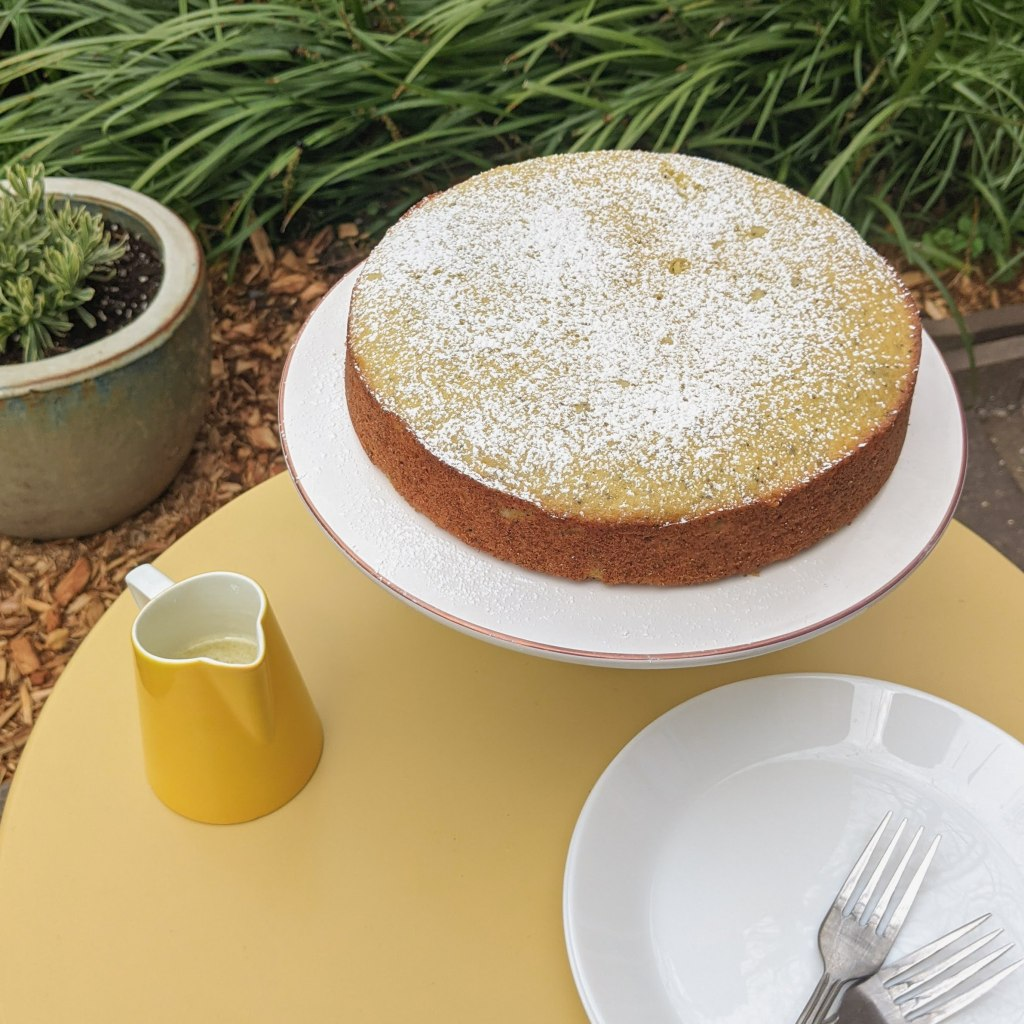 A round lemon-poppyseed cake on a cake stand, with a small pitcher of glaze and a stack of plates next to it