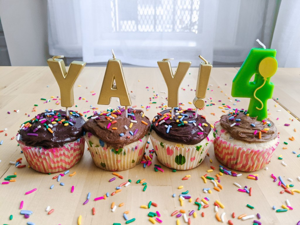 """Four chocolate-frosted cupcakes with candles that read """"YAY!"""" and a #4 candle with a balloon on it."""