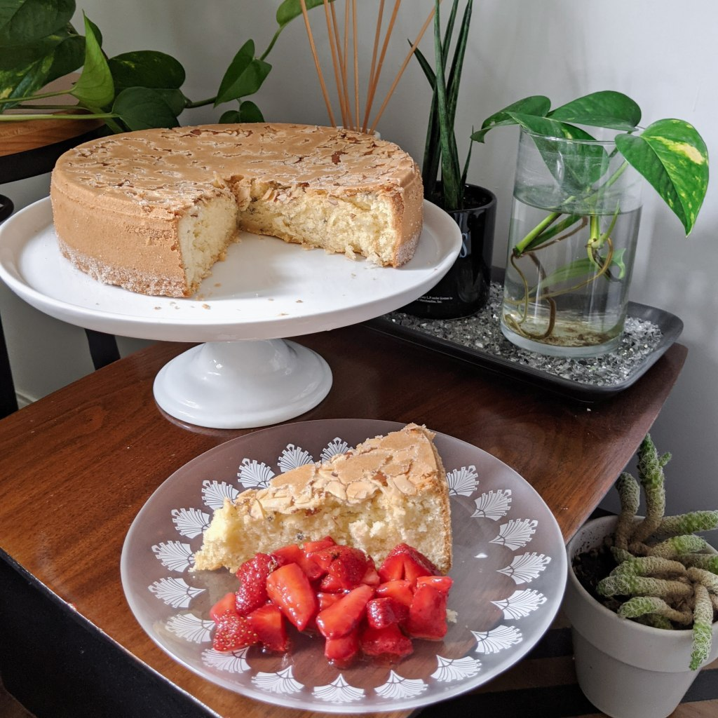An almond-topped cake on a stand, with a slice cut out. The slice is on a plate with strawberries next to the stand.