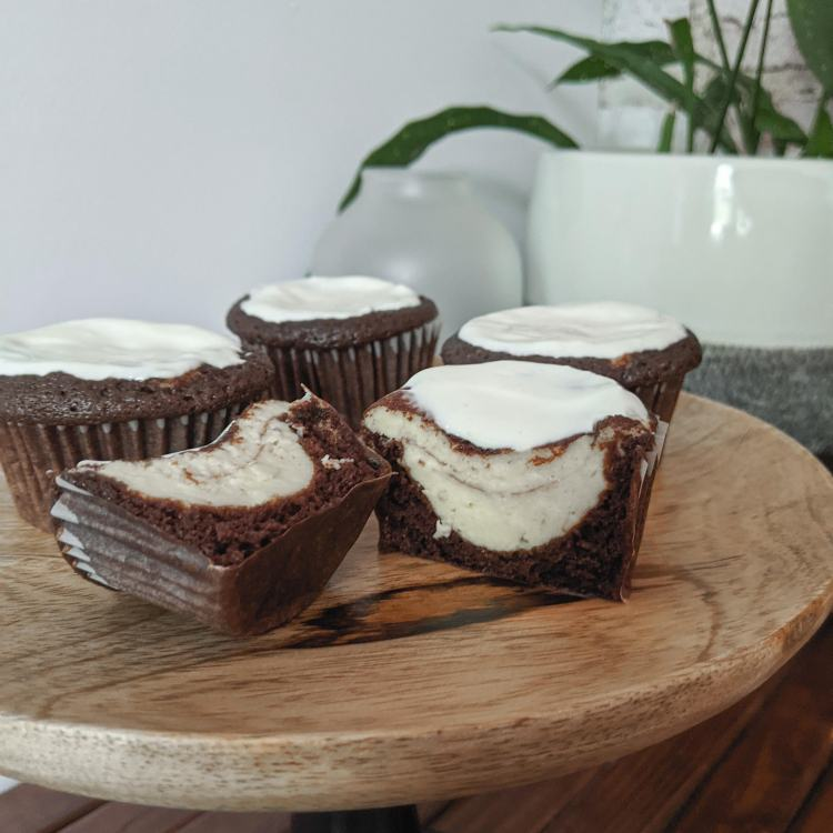 Four chocolate cupcakes with sour cream topping; one is sliced in half to reveal a cheesecake center