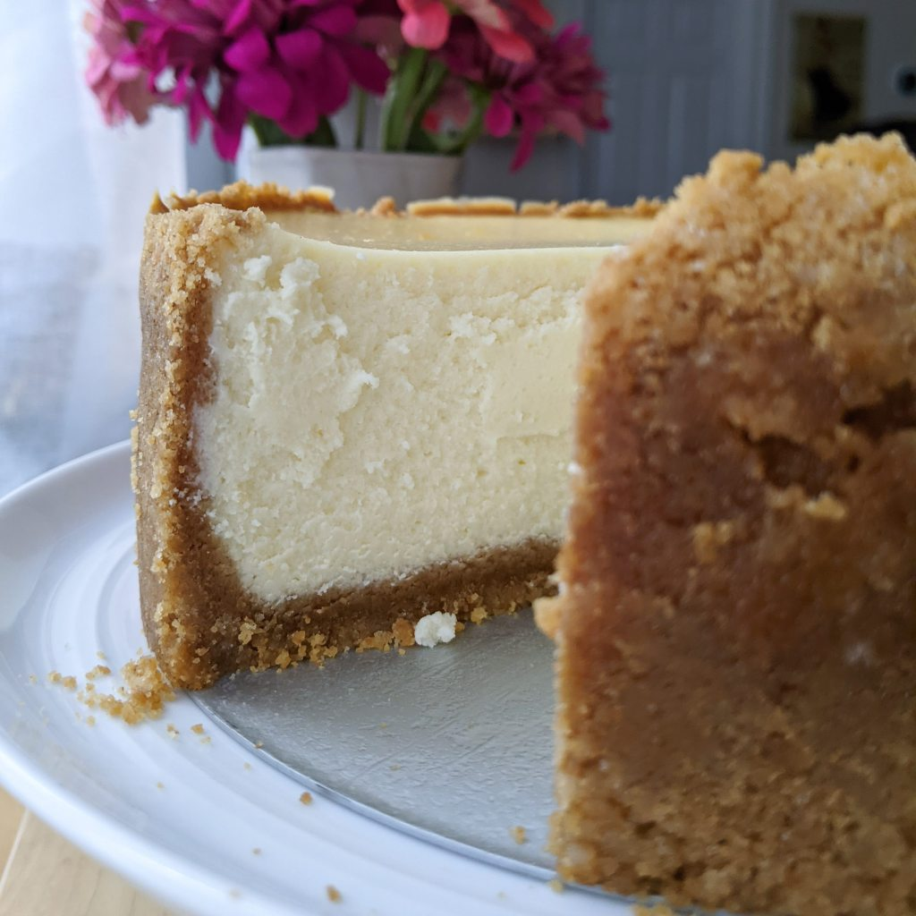 A close-up of tall cheesecake with a slice cut out